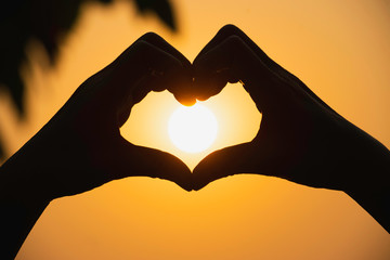 Hands of person make  heart by finger in silhouette sunset  background.