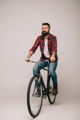 handsome bearded man in checkered shirt riding bicycle on grey