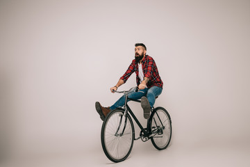 bearded excited man riding bike isolated on grey