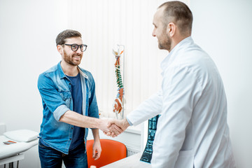 Man as a patient handshaking with senior doctor visiting therapist office