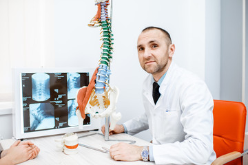 Portrait of a senior therapist sitting with anatomical model of the human spine in the medical office