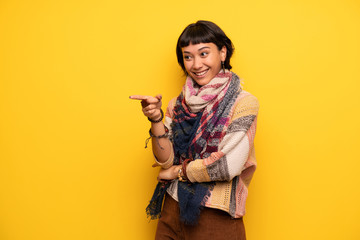 Young hippie woman over yellow wall pointing finger to the side in lateral position
