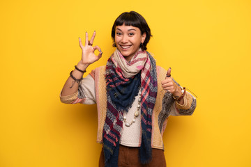 Young hippie woman over yellow wall showing ok sign with and giving a thumb up gesture