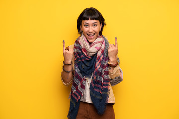 Young hippie woman over yellow wall pointing with the index finger a great idea