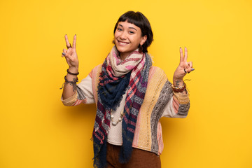 Young hippie woman over yellow wall smiling and showing victory sign with both hands