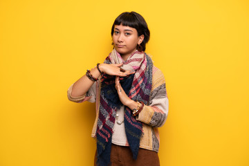 Young hippie woman over yellow wall making stop gesture with her hand to stop an act