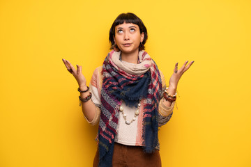 Young hippie woman over yellow wall frustrated by a bad situation