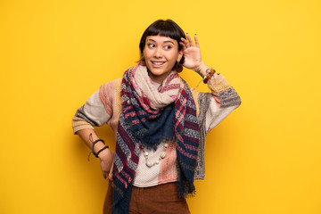 Young hippie woman over yellow wall listening to something by putting hand on the ear