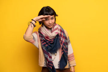 Young hippie woman over yellow wall looking far away with hand to look something