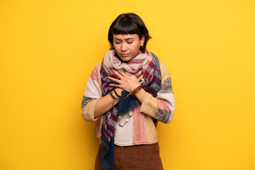 Young hippie woman over yellow wall having a pain in the heart