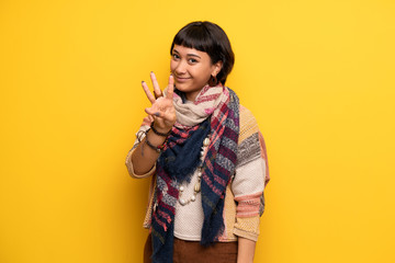 Young hippie woman over yellow wall happy and counting three with fingers