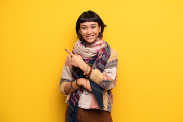 Young hippie woman over yellow wall pointing to the side to present a product
