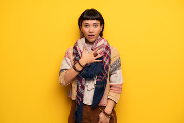 Young hippie woman over yellow wall surprised and shocked while looking right