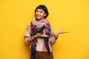 Young hippie woman over yellow wall presenting an idea while looking smiling towards