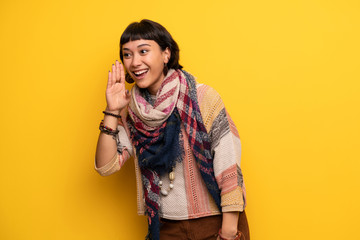 Young hippie woman over yellow wall shouting with mouth wide open to the lateral