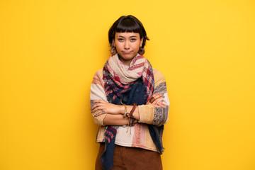 Young hippie woman over yellow wall feeling upset