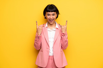 Modern woman with pink business suit making rock gesture