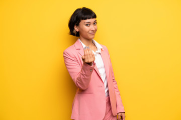 Modern woman with pink business suit inviting to come with hand. Happy that you came