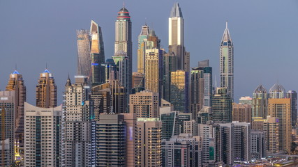 Dubai marina with traffic on sheikh zayed road panorama day to night timelapse lights turn on.