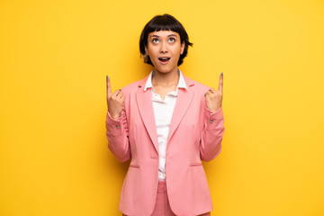 Modern woman with pink business suit surprised and pointing up
