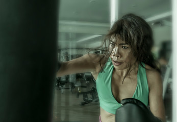 young athletic and fit attractive Asian fighter woman punching heavy bag with boxing gloves at fight club gym doing hard workout sweaty and furious learning attack