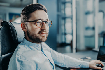 bearded trendy modern business man at work in office. manager with glasses.