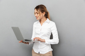 Photo of businesslike woman in formal wear standing and holding laptop in the office, isolated over gray background