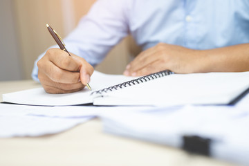 close up hand business man are sitting using pen writing record lecture  income and expenses accounting document note pad into the book on the table wood in office.