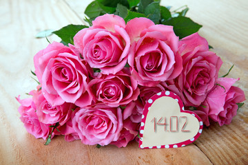 Valentine's Day background with pink roses over wooden table.