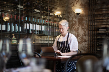 Female chef working on digital tablet in restaurant
