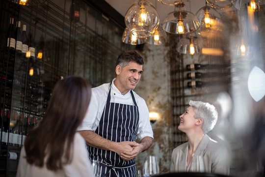 Chef greeting customers in his restaurant