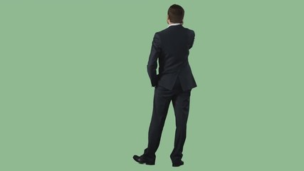324686b708e 0:24 Young man in dark blue business suit is standing and talking by  cellphone. Green screen