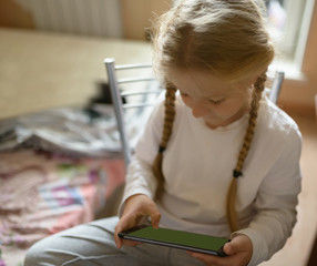 Girl playing with tablet pc. Selective focus on pda.