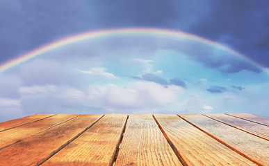 Empty surface of a wooden table on a rainbow background