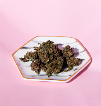 Cannabis flower on marble plate with pink background