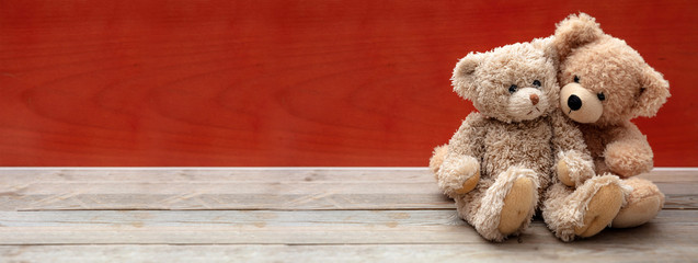 Love, friendship concept, tight hug. Teddy bears couple on wooden floor, red wall background, banner.