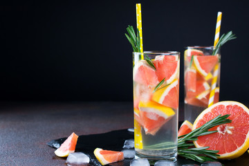 Grapefruit lemonade. Two glasses of refreshing drink, water with  grapefruit, rosemary branches and ice. Recipe concept, cocktail
