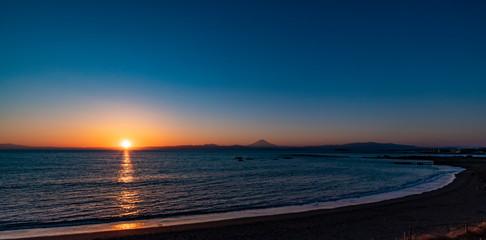 夕焼けの富士山を湘南の海岸越しに撮影