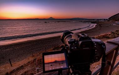夕焼けの富士山を湘南の海岸越しに撮影中