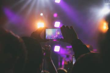 Hand hold a smart phone taking photo or recording video of concert stage
