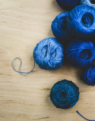blue threads on a wooden background blue embroidery threads