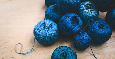 Bright blue threads for embroidery and sewing lie on a wooden background threads on a light background