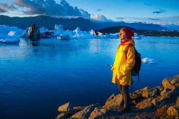 Woman in bright yellow raincoat near the Glacier Lagoon, Iceland