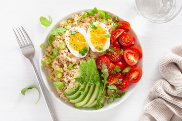 quinoa with boiled egg, avocado, tomato, arugula. healthy breakfast