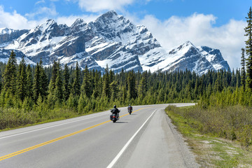Riding On The Icefields Parkway - Two motorcyclists are enjoying the scenic ride on Icefields Parkway, with massive snow-covered Mount Patterson rising high in front of road, Banff National Park, AB.