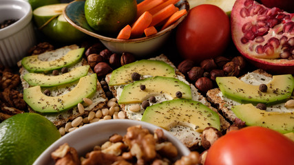 Crispbread with cheese and avocado, tomatoes, nuts, fruits, salad, spices on dark board background top view. Food and Health