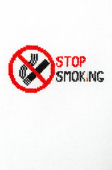 Stop smoking Sign of a stop of a cigarette embroidered on a white fabric.