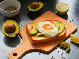 Grilled bread topping with avocado sliced and fried egg on wooden chopping board for healthy  breakfast concept.