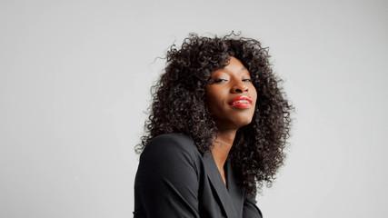 portrait of black woman in studio wear office black tie and red lipstick