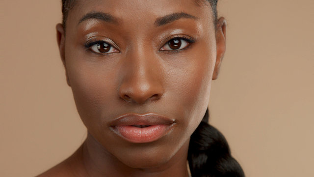 closeup portrait of mixed race black woman watching to the camera. Ideal skin, natural makeup, shiny glossy eyelids